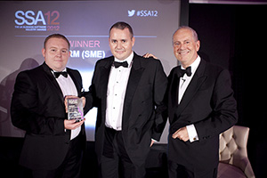 Customers Service Director Matthew Ruddle and CEO James White collecting the award, presented by Gyles Brandreth